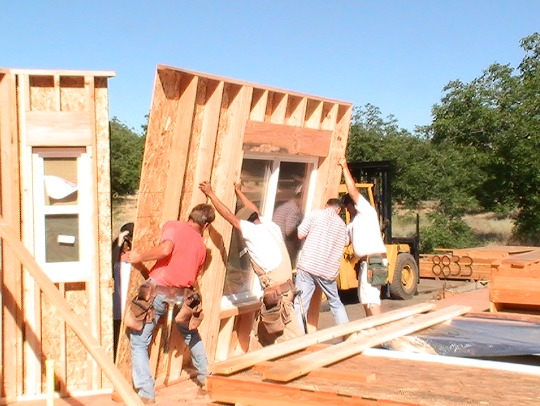 Wall panels with the window installed is lifted into place by crew