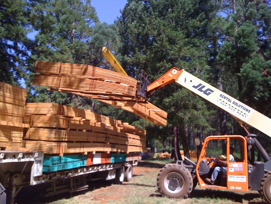 roof trusses being unloaded at the job site for a panelized framing kit